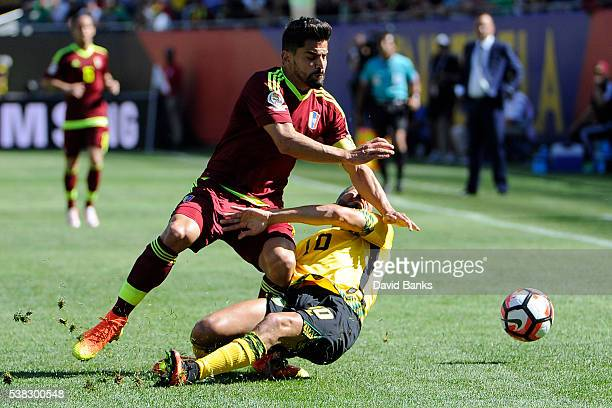 Tomas Rincon of Venezuela and Jobi McAnuff of Jamaica go for the ball during the first half during a group C match between Jamaica and Venezuela at...