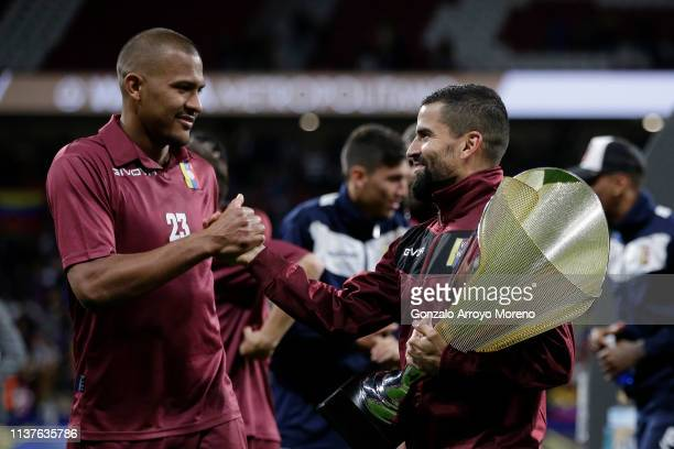 Tomas Rincon of Venezuela holds the trophy and shakes hands with Salomon Rondon of Venezuela after their team win the International Friendly match...