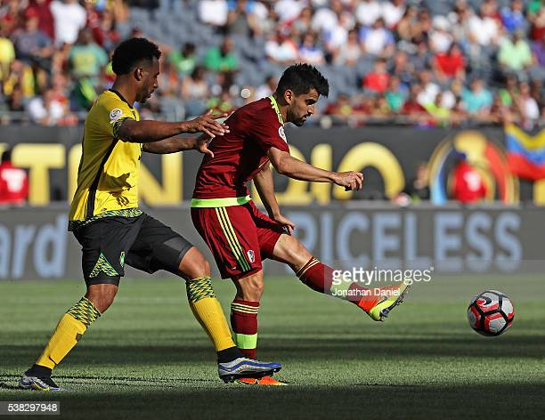Tomas Rincon of Venezuela passes the ball under presure from Giles Barnes of Jamaica during a match in the 2016 Copa America Centenario at Soldier...