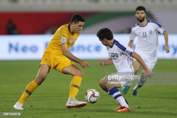Tomas Rogic of Australia battles for possession with Javokhir Sidikov of Uzbekistan during the AFC Asian Cup round of 16 match between Australia and...