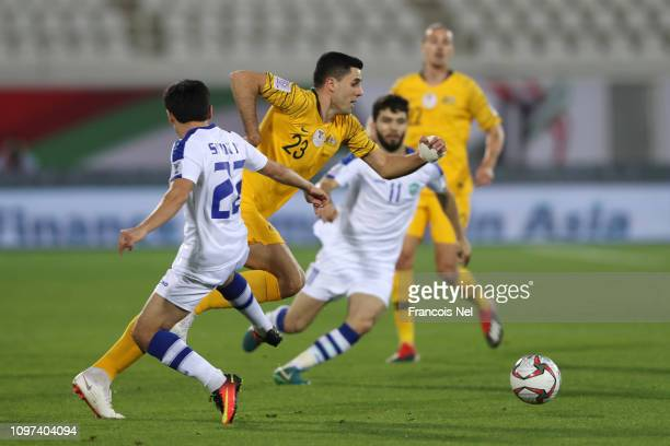 Tomas Rogic of Australia is challanged by Javokhir Sidikov of Uzbekistan during the AFC Asian Cup round of 16 match between Australia and Uzbekistan...