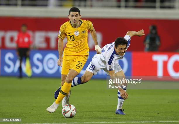 Tomas Rogic of Australia shoots while challenged by Otabek Shukurov of Uzbekistan during the AFC Asian Cup round of 16 match between Australia and...