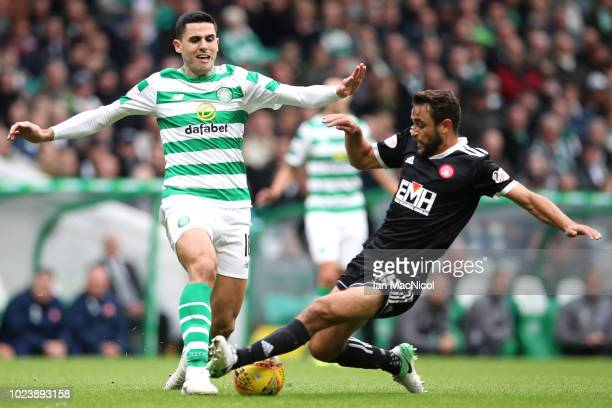 Tomas Rogic of Celtic is challenged by Tom Taiwo of Hamilton Academical during the Scottish Premier League match between Celtic and Hamilton at...