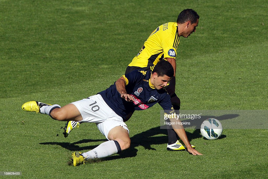 Tomas Rogic of the Mariners goes down while tackling Leo Bertos of the Phoenix during the round 12 A-League match between the Wellington Phoenix and the Central Coast Mariners at Westpac Stadium on December 22, 2012 in Wellington, New Zealand.