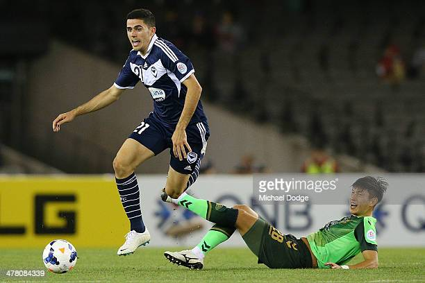 Tomas Rogic of the Victory runs with the ball past Lee Gang Jin of Joenbuk contest for the ball during the AFC Asian Champions League match between...