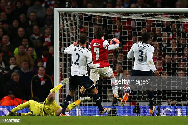 Tomas Rosicky of Arsenal chips the ball over goalkeeper Hugo Lloris of Spurs to score his team'ssecond goal during the Budweiser FA Cup third round...