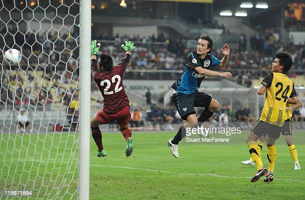 Tomas Rosicky of Arsenal heads past Mohd Nasril of Malaysia to score the 4th goal during the pre-season Asian Tour friendly match between Malaysia...