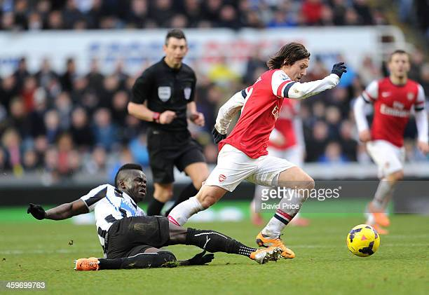 Tomas Rosicky of Arsenal is challenged by Cheick Tiote of Newcastle during the Barclays Premier League match between Newcastle United and Arsenal at...