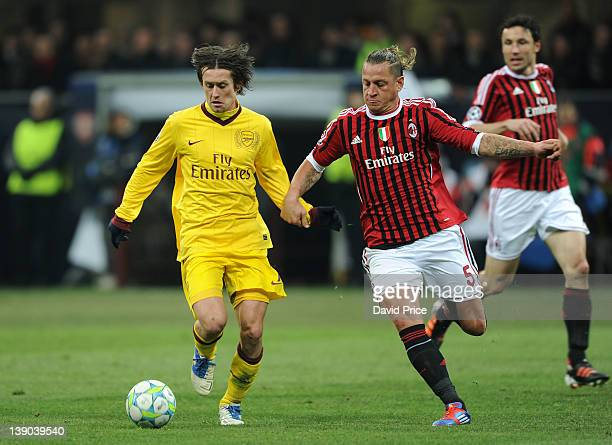 Tomas Rosicky of Arsenal is held back by Philippe Mexes of Milan during the UEFA Champions League Round of 16 match between AC Milan and Arsenal FC...