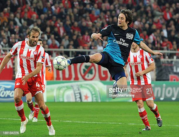 Tomas Rosicky of Arsenal jumps above Olof Mellberg of Olympiacos during the UEFA Champions League Group F match between Olympiacos FC and Arsenal FC...