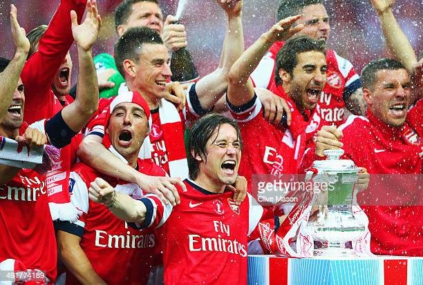 Tomas Rosicky of Arsenal leads the trophy celebrations after the FA Cup with Budweiser Final match between Arsenal and Hull City at Wembley Stadium...