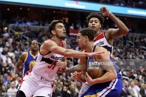 Tomas Satoransky and Kelly Oubre Jr #12 of the Washington Wizards trap Klay Thompson of the Golden State Warriors in the first half at Verizon Center...