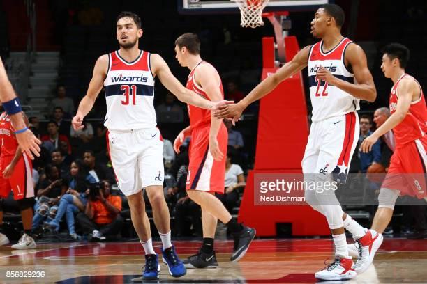 Tomas Satoransky of the Washington Wizards and Otto Porter Jr #22 of the Washington Wizards share a congratulatory shake during the preseason game...