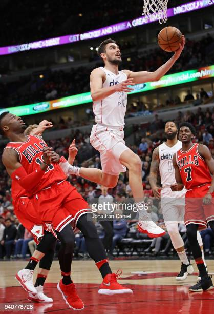 Tomas Satoransky of the Washington Wizards drives to the basket over David Nwaba of the Chicago Bulls at the United Center on April 1 2018 in Chicago...