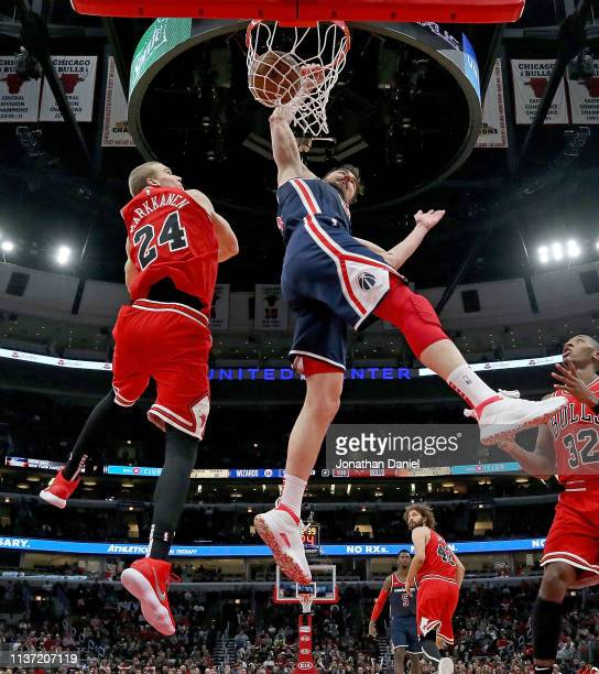 Tomas Satoransky of the Washington Wizards dunks over Lauri Markkanen of the Chicago Bulls at the United Center on March 20 2019 in Chicago Illinois...