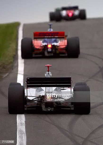 Tomas Scheckter driver of the Vision Racing Dallara Honda chases Ryan Briscoe driver of the Dreyer Reinbold Dallara Honda during the Indy Racing...