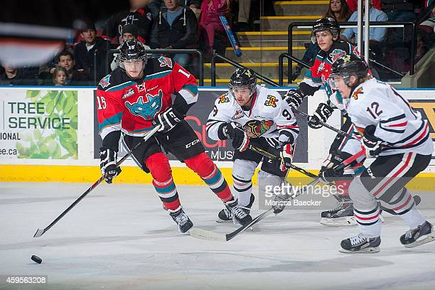 Tomas Soustal of Kelowna Rockets passes the puck as Chase De Leo and Miles Koules of Portland Winterhawks check on November 21 2014 at Prospera Place...