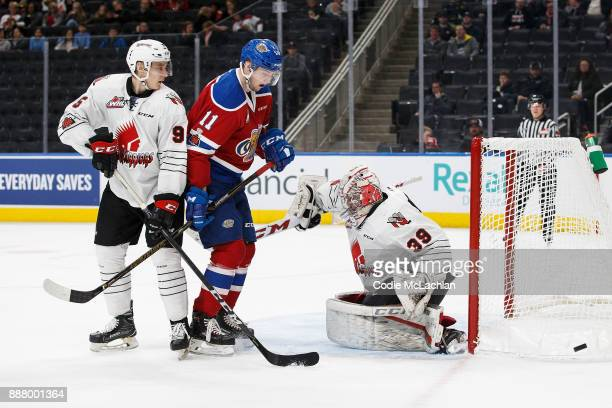 Tomas Soustal of the Edmonton Oil Kings looks for an opportunity as Dmitri Zaitsev and goaltender Adam Evanoff of the Moose Jaw Warriors defend at...