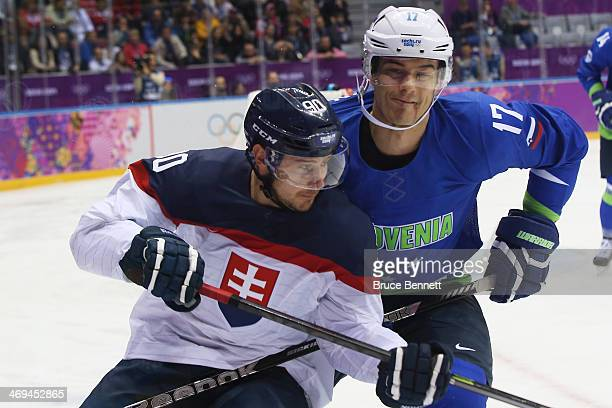 Tomas Tatar of Slovakia skates against Ziga Pavlin of Slovenia in the first period during the Men's Ice Hockey Preliminary Round Group A game on day...