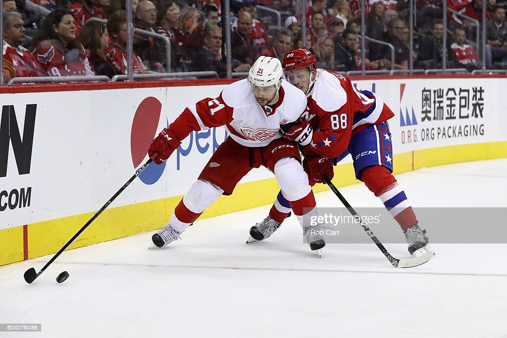 Tomas Tatar #21 of the Detroit Red Wings and Nate Schmidt #88 of the Washington Capitals go after the puck in the third period at Verizon Center on November 18, 2016 in Washington, DC.