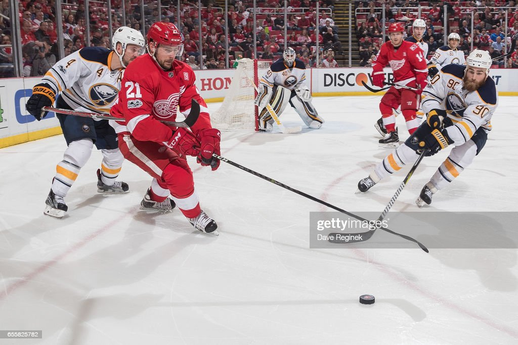 Tomas Tatar #21 of the Detroit Red Wings and Ryan O'Reilly #90 of the Buffalo Sabres both reach for the puck during an NHL game at Joe Louis Arena on March 20, 2017 in Detroit, Michigan. The Sabres defeated the Wings 2-1.