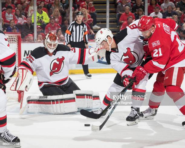 Tomas Tatar of the Detroit Red Wings battle for the puck in front of the goaltender Cory Schneider of the New Jersey Devils with Beau Bennett of the...