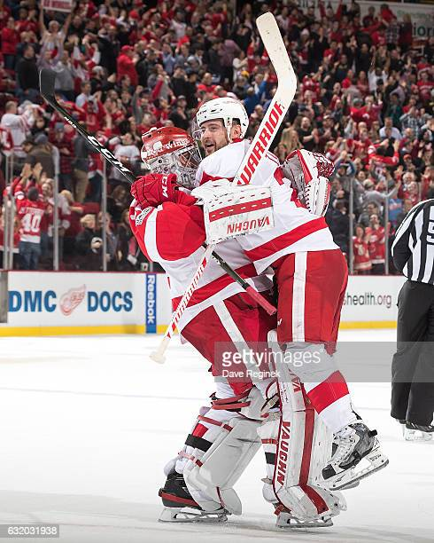 Tomas Tatar of the Detroit Red Wings jumps into the arms of teammate goaltender Petr Mrazek of the Detroit Red Wings following their shootout win of...