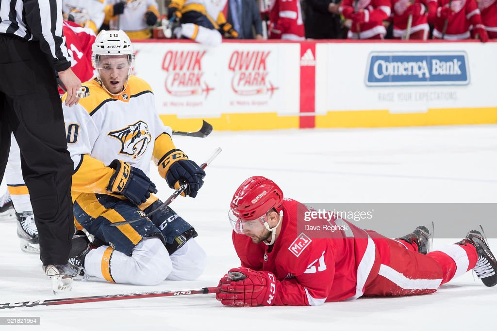 Tomas Tatar #21 of the Detroit Red Wings lays on the ice dejected after the final seconds of the game next to Colton Sissons #10 of the Nashville Predators following an NHL game at Little Caesars Arena on February 20, 2018 in Detroit, Michigan. The Predators defeated the Wings 3-2.
