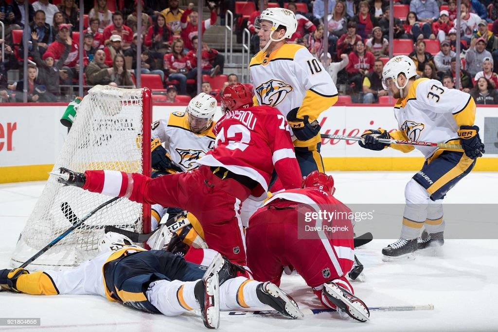 Tomas Tatar #21 of the Detroit Red Wings pokes in the puck for a third period goal on Juuse Saros #74 of the Nashville Predators as teammates Ryan Ellis #4, Colton Sissons #10 and Viktor Arvidsson #33 defend against Andreas Athanasiou #72 and Justin Abdelkader #8 of the Wings during an NHL game at Little Caesars Arena on February 20, 2018 in Detroit, Michigan.