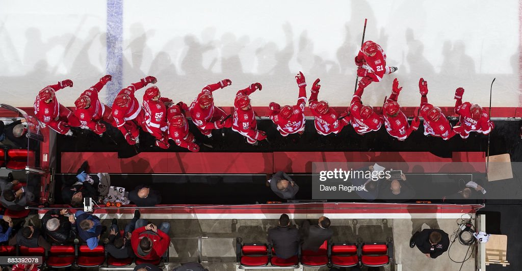 Tomas Tatar #21 of the Detroit Red Wings pounds gloves with teammates on the bench following his first period goal during an NHL game against the Montreal Canadiens at Little Caesars Arena on November 30, 2017 in Detroit, Michigan. The Canadiens defeated the Red Wings 6-3.