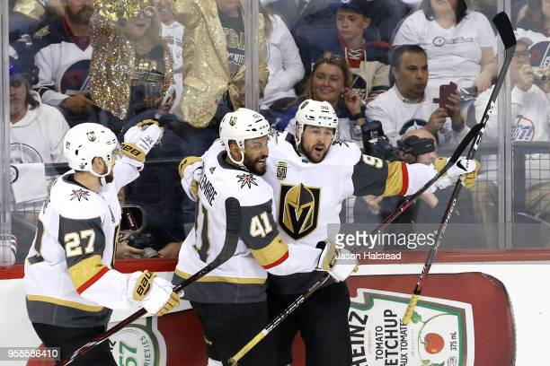 Tomas Tatar of the Vegas Golden Knights is congratulated by his teammates Shea Theodore and PierreEdouard Bellemare after scoring a first period goal...