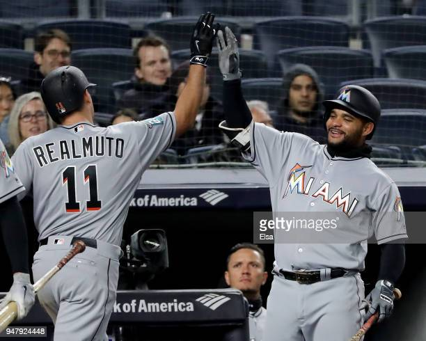 Tomas Telis of the Miami Marlins congratulates teamamte JT Realmuto after Realmuto hit a three run home run in the fifth inning against the New York...