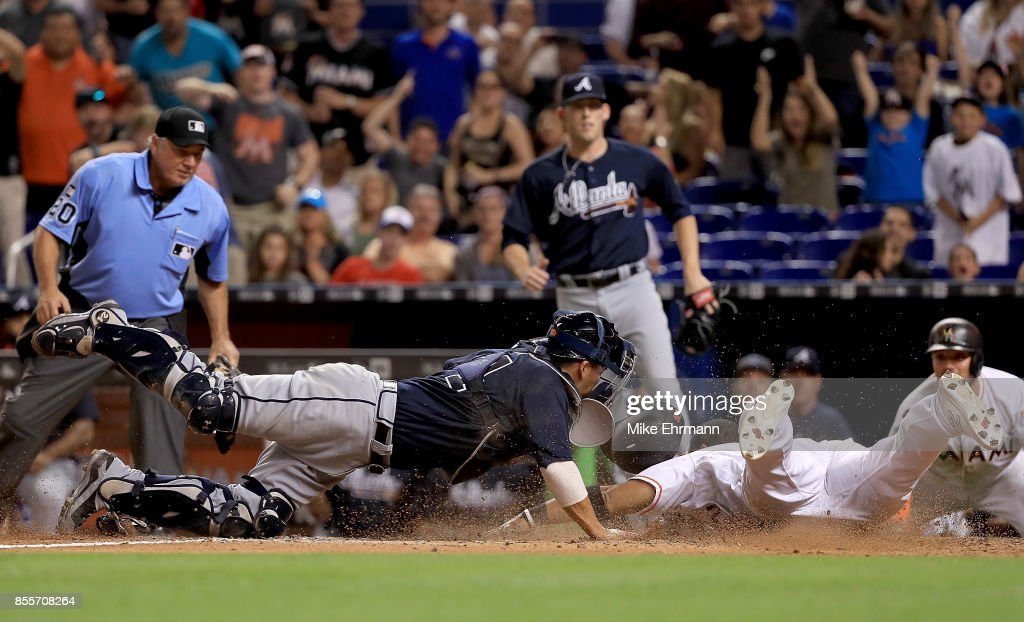 Tomas Telis #18 of the Miami Marlins is tagged out at home by Kurt Suzuki #24 of the Atlanta Braves during a game at Marlins Park on September 29, 2017 in Miami, Florida.