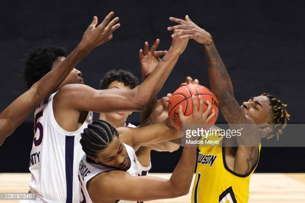 Tomas Woldetensae of the Virginia Cavaliers grabs a rebound in front of Demetrius Mims of the Towson Tigers during the second half at Mohegan Sun...