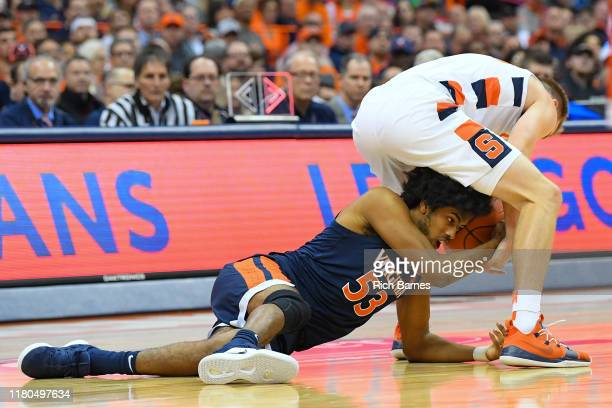 Tomas Woldetensae of the Virginia Cavaliers reaches for the ball between the legs of Buddy Boeheim of the Syracuse Orange during the second half at...