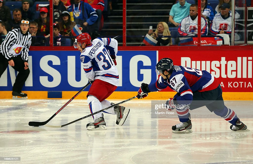 Tomas Zaborsky (R) of Slovakia and Alexander Perezhogin (L) of Russia battle for the puck during the IIHF World Championship group H match between Slovakia and Russia at Hartwall Areena on May 12, 2013 in Helsinki, Finland.