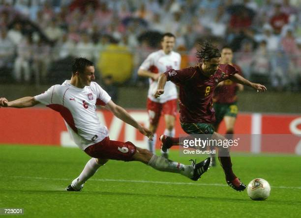 Tomasz Hajto of Poland tackles Joao Pinto of Portugal during the Group D match of the World Cup Group Stage played at the Jeonju World Cup Stadium,...