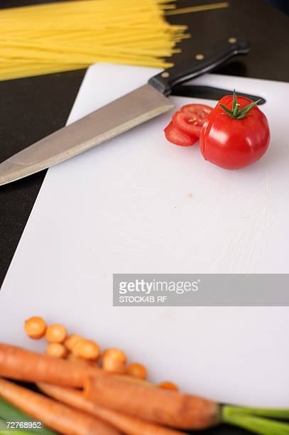 tomato and carrots on a carving board next to a kitchen knife, high angle view - carving knife stock pictures, royalty-free photos & images