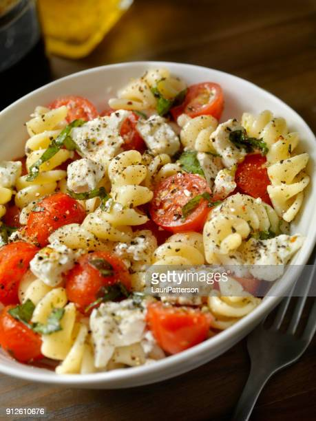 tomato and feta, pasta salad with freshly chopped basil - side salad stock pictures, royalty-free photos & images