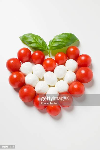 Tomato and mozzarella in heart shape with basil leaves.