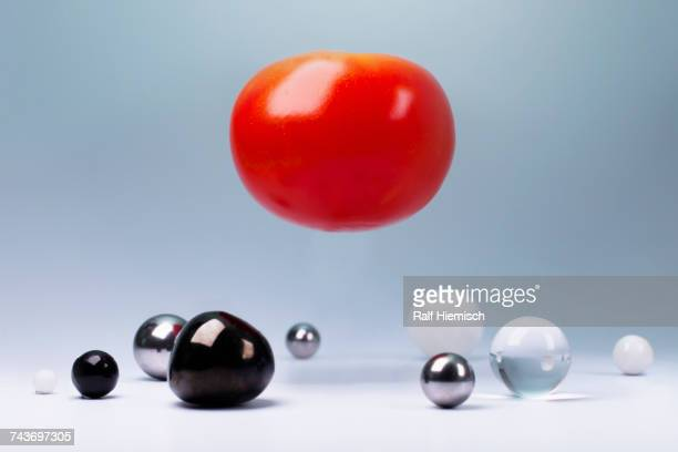 Tomato in mid-air over small round objects below against gray background