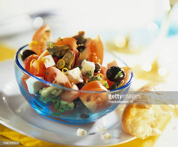 Tomato, mussel, feta and olive salad in bowl, close-up