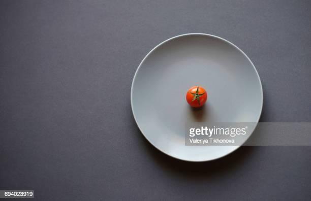 tomato on white plate - einfachheit stock-fotos und bilder