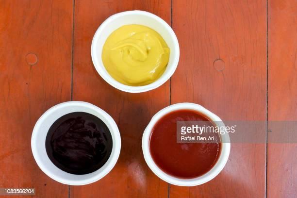 tomato sauce mustard and bbq sauce on a wooden table - rafael ben ari stock-fotos und bilder