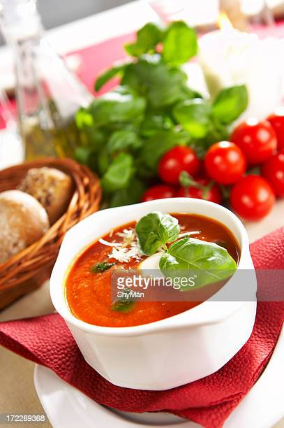 Tomato soup with basil, fresh tomatoes, and bread in basket