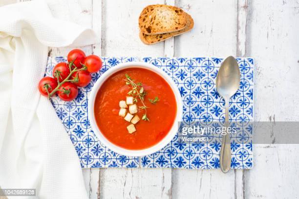 tomato soup with roasted bread, croutons and thyme, overhead view - tomato soup stock photos and pictures