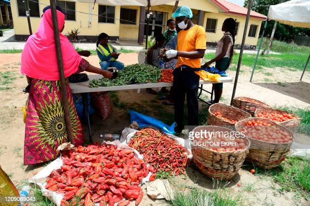 A tomato vendor attends to buyer at a Primary School converted for a temporary makeshift food market established by Lagos State government for...