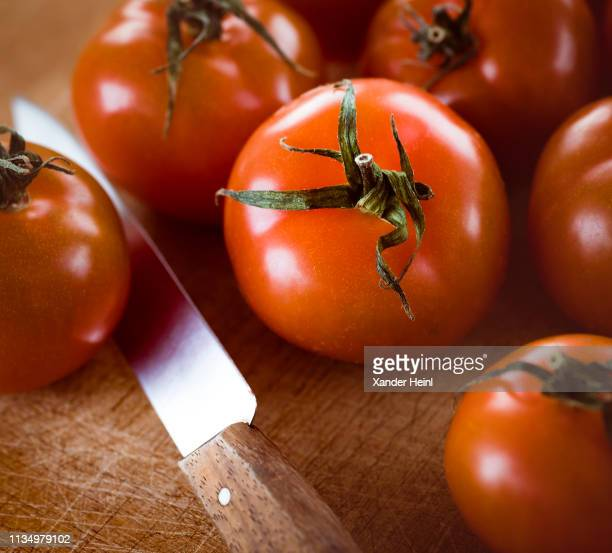 Tomatoes and a knife lie on a wooden board on February 07 2019 in Berlin Germany