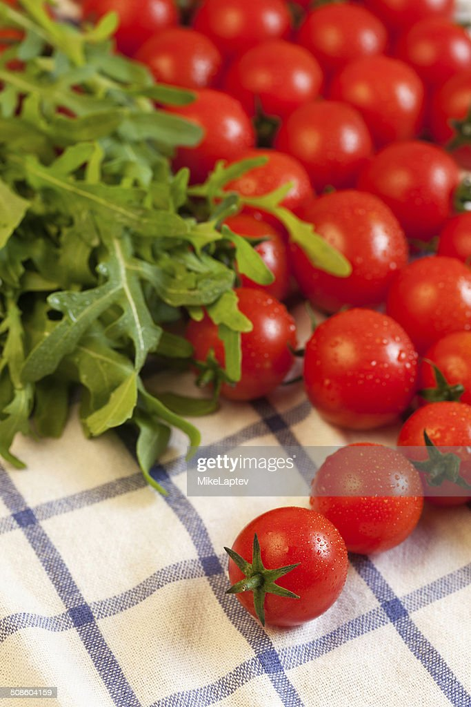 Tomatoes and arugula on towel : Stock Photo