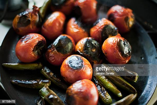 Tomatoes and chilis being grilled in a stove